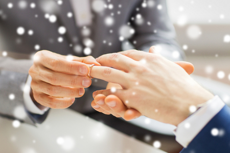 homosexual sex: people, homosexuality, same-sex marriage and love concept - close up of happy male gay couple hands putting wedding ring on over snow effect
