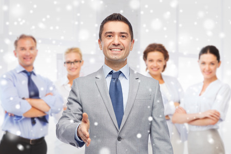 business, people, gesture, partnership and greeting concept - happy smiling businessman in suit with team giving hand for handshake over office room background and snow effect