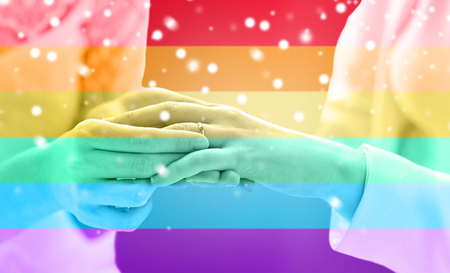 same sex: people, homosexuality, same-sex marriage and love concept - close up of happy lesbian couple hands putting on wedding ring over rainbow flag stripes background over snow effect