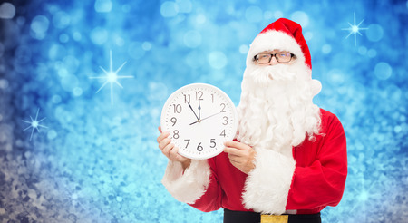 12 month old: christmas, holidays, time and people concept - man in costume of santa claus with clock showing twelve over blue glitter or lights background