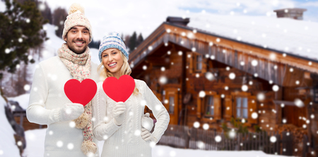 x country: love, valentines day, couple, christmas and people concept - smiling man and woman in winter hats and scarf holding red paper heart shape over wooden country house and snow background
