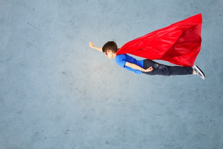 child boy: happiness, freedom, childhood, movement and people concept - boy in red superhero cape and mask flying in air over gray concrete background Stock Photo