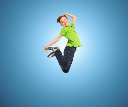pre adolescent boys: happiness, childhood, freedom, movement and people concept - smiling boy jumping in air over blue background