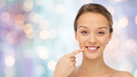 beauty, people, dental care and hygiene concept - happy young woman pointing finger to her smile or teeth over purple holidays lights background