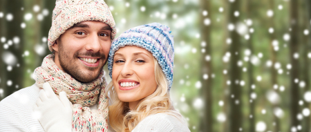christmas winter: winter, fashion, couple, christmas and people concept - smiling man and woman in hats and scarf hugging over snow and forest background