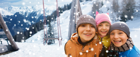 x country: childhood, friendship, winter holidays, vacation and people concept - group of happy kids hugging over swing and snowy mountains background