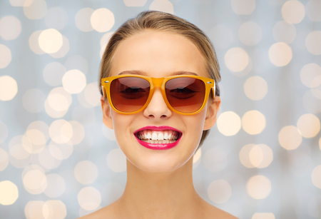 gloss: beauty, people, accessory and fashion concept - smiling young woman in sunglasses with pink lipstick on lips over holidays lights background Stock Photo