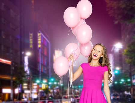 street party: people, holidays, party, nightlife and fashion concept - happy young woman or teen girl in pink dress with helium air balloons over night city street background
