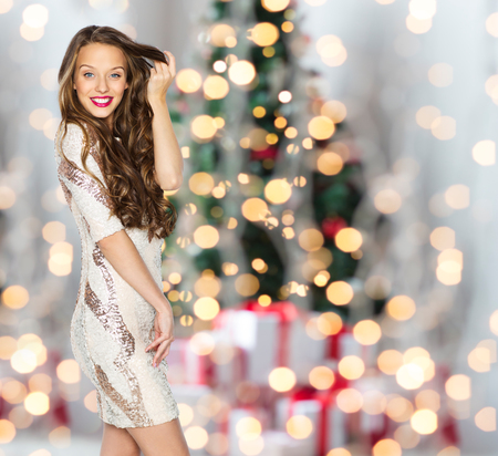 people, holidays, hairstyle and fashion concept - happy young woman or teen girl in fancy dress with sequins touching long wavy hair over christmas tree lights background Stock Photo
