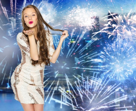 kisses: people, style, holidays, hairstyle and fashion concept - happy young woman or teen girl in fancy dress with sequins and long wavy hair sending blow kiss over firework at night city background Stock Photo