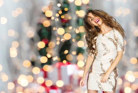 donna che balla: la gente, le vacanze, il partito e il concetto di moda - felice giovane donna o adolescente ragazza in abito fantasia con paillettes e lunghi capelli ondulati ballare nel periodo di Natale sfondo di luci albero