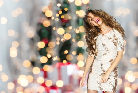 winter people: people, holidays, party and fashion concept - happy young woman or teen girl in fancy dress with sequins and long wavy hair dancing over christmas tree lights background Stock Photo