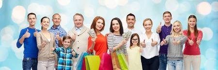 grupo de hombres: gesto, venta, compras y concepto de la gente - grupo de sonriente de hombres, mujeres y niños que muestran los pulgares hacia arriba y la celebración de bolsas de la compra con el dinero durante las vacaciones luces de fondo azul