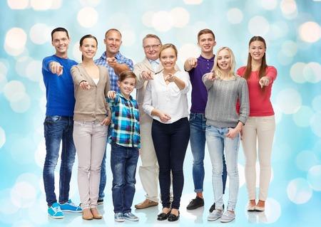 Familie, geslacht, generatie en gebaarconcept - groep gelukkige mensen die vinger op u wijzen op blauwe vakantiedagen achtergrond