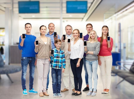 youth group: family, technology, travel and tourism concept - group of smiling people with smartphones over airport waiting room background