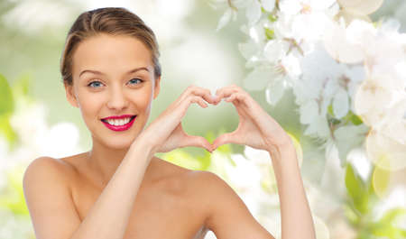 natural beauty: beauty, people, love, valentines day and make up concept - smiling young woman with pink lipstick on lips showing heart shape hand sign over summer green natural background with cherry blossom Stock Photo