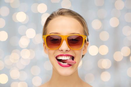 mensen, uitdrukking, vreugde en mode concept - lachende jonge vrouw in een zonnebril met roze lippenstift op de lippen toont tong over vakantie steekt achtergrond aan