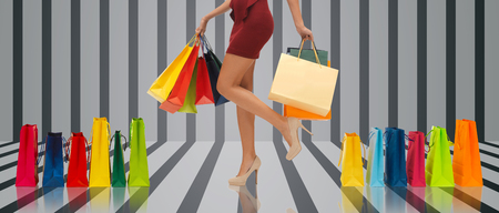 body dimensions: people, sale and consumerism concept - close up of woman in red short skirt and high heeled shoes with shopping bags over gray striped 3d background Stock Photo