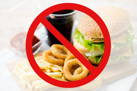 low carb diet: fast food, low carb diet, fattening and unhealthy eating concept - close up of hamburger or cheeseburger, deep-fried squid rings and french fries behind no symbol or circle-backslash prohibition sign