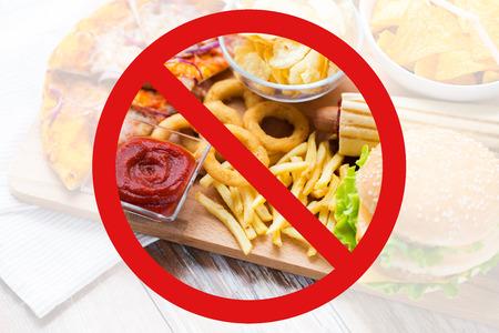 comida rápida, dieta baja en carbohidratos, engorde y poco saludable concepto de alimentación - cerca de los anillos de calamares fritos, papas fritas y otros aperitivos detrás de ningún símbolo o un círculo-barra invertida señal de prohibición