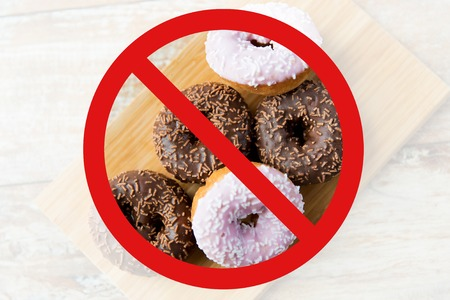 no food: fast food, low carb diet, fattening and unhealthy eating concept - close up of glazed donuts on wooden board behind no symbol or circle-backslash prohibition sign Stock Photo