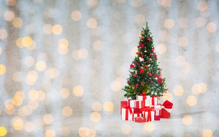 x mas: celebration, winter holidays and advertisement concept - christmas tree with gifts and santa hat over concrete wall background