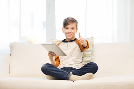 pre approval: leisure, children, technology and people concept - smiling boy with tablet pc computer showing thumbs up at home Stock Photo