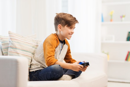 pre adolescent boy: leisure, children, technology and people concept - smiling boy with joystick playing video game at home