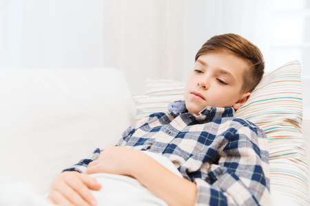 childhood, healthcare, people and medicine concept - ill boy with flu lying in bed at home