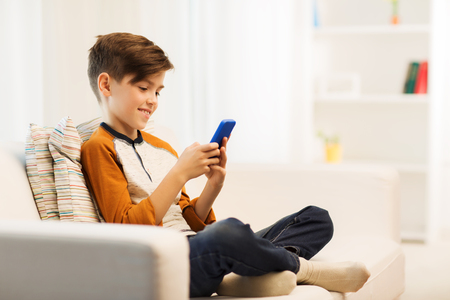 pre teen boys: leisure, children, technology, internet communication and people concept - smiling boy with smartphone texting message or playing game at home