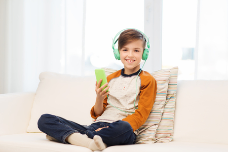 pre adolescent boy: leisure, children, technology and people concept - smiling boy with smartphone and headphones listening to music at home