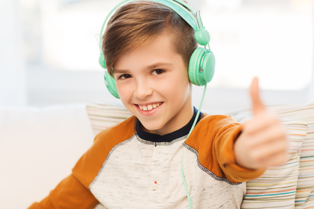pre adolescent boy: leisure, children, technology, gesture and people concept - smiling boy with headphones listening to music and showing thumbs up at home Stock Photo