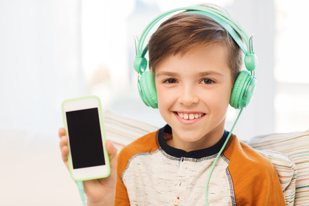 pre adolescent boy: leisure, children, technology, advertisement and people concept - smiling boy with smartphone and headphones listening to music at home