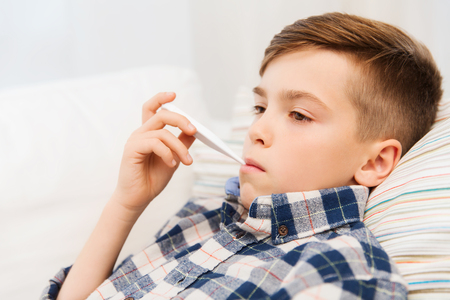 sad child: childhood, healthcare and medicine concept - ill boy with flu measuring temperature by thermometer at home