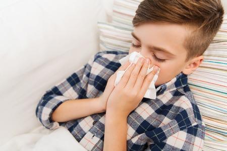 gripe: la infancia, la salud, la rinitis, la gente y concepto de la medicina - ni�o enfermo con la gripe que miente en la cama y soplar la nariz en el hogar
