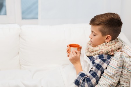 bacterial infection: childhood, healthcare, people and medicine concept - ill boy with flu lying in bed and drinking tea at home