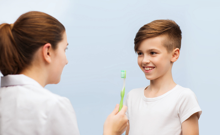 dentist concept: medicine, health care, dentistry, hygiene and people concept - doctor or dentist with toothbrush and happy boy in clinic Stock Photo
