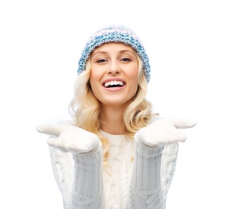 winter people: winter, advertisement, christmas and people concept - smiling young woman in winter hat and sweater holding something on her empty palms Stock Photo