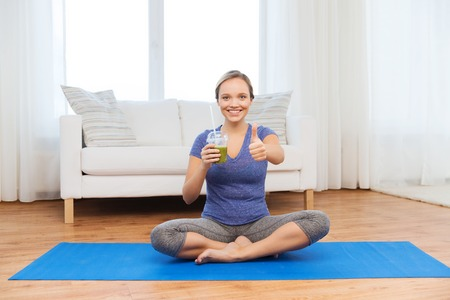 mat like: fitness, sport, people, diet and healthy lifestyle concept - happy woman with cup of smoothie sitting on mat at home and showing thumbs up