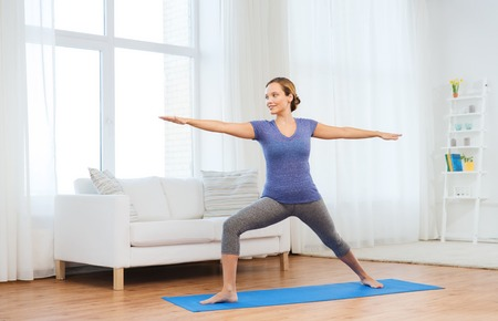 warrior pose: fitness, sport, people and healthy lifestyle concept - woman making yoga warrior pose on mat Stock Photo