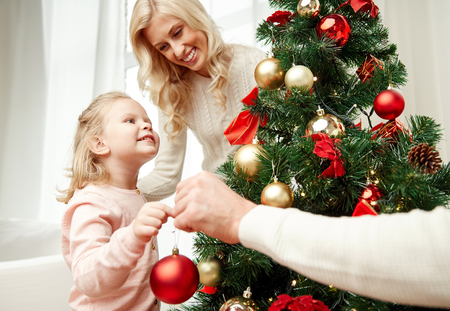 decorating christmas tree: family, x-mas, winter holidays and people concept - happy mother, father and little daughter decorating christmas tree at home