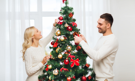home decorating: family, x-mas, winter holidays and people concept - happy couple decorating christmas tree at home
