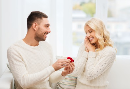 couple home: love, christmas, couple, proposal and people concept - happy man giving engagement ring in little red box to woman at home