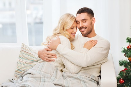love hug: family, love, winter holidays, christmas and people concept - happy couple hugging on sofa at home