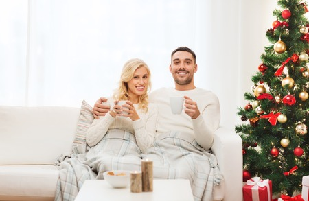 family sofa: family, christmas, holidays, love and people concept - happy couple covered with plaid drinking tea and sitting on sofa at home