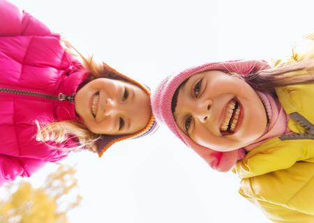 niños sonriendo: la infancia, el ocio, la amistad y el concepto de la gente - niñas felices enfrenta al aire libre