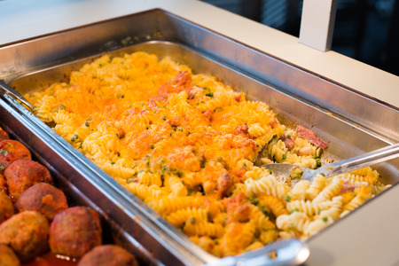 catering food: food, catering, self-service and eating concept - close up of pasta and meatballs on metallic tray Stock Photo