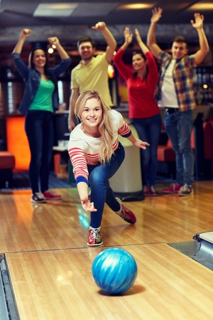 ball: people, leisure, sport and entertainment concept - happy young woman throwing ball in bowling club