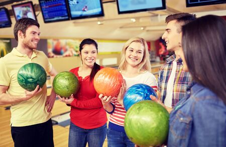 entertainment concept: people, leisure, sport, friendship and entertainment concept - happy friends holding balls and talking in bowling club Stock Photo