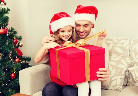 christmas hat: family, christmas, x-mas, happiness and people concept - smiling father and daughter in santa helper hats opening gift box